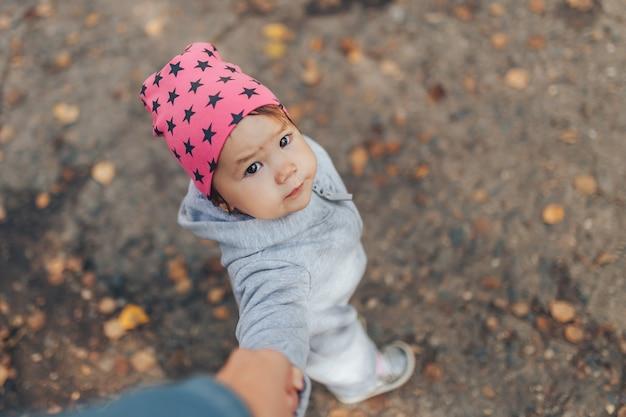 スタイリッシュなオーバーオールを着て屋外を歩いてかわいい1歳の女の赤ちゃん Premium写真