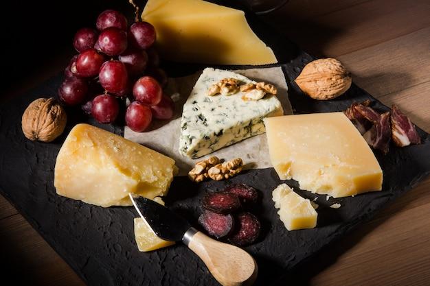盛り合わせチーズ、ナッツ、ブドウ、フルーツ、スモーク肉、ワイン1杯。ダークでムーディーなスタイル。テキスト用の空き容量。 Premium写真