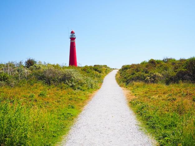 ノースタワー-シエルモニコーフ島の灯台、フリジア諸島の1つ、青い空を背景に砂丘の上の灯台 Premium写真