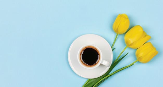 ソーサーにブラックコーヒーを1杯と花束の花黄色のチューリップ Premium写真