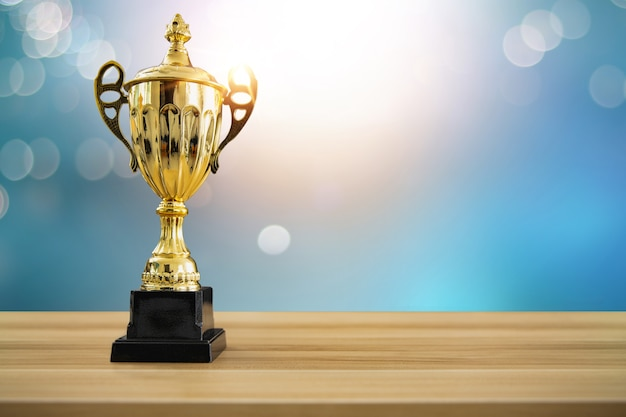 1st champion award, the best prize and winner concept, championship cup or winner trophy on wood table with soft blue and bokeh background Premium Photo