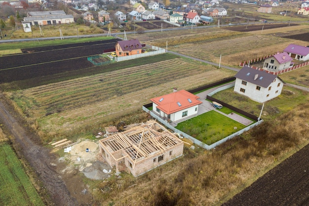 2つの民家を上から見下ろした空中写真。1つは木製の屋根のフレームで、もう1つは赤瓦の屋根で仕上げられています。 Premium写真