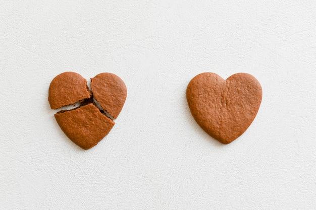 2つのハート型のクッキー、そのうちの1つは白い背景に壊れています。ハート型のcookieをクラックして、関係を破壊し、終了する概念、片思いを愛します。報われない愛の概念.. valenti Premium写真