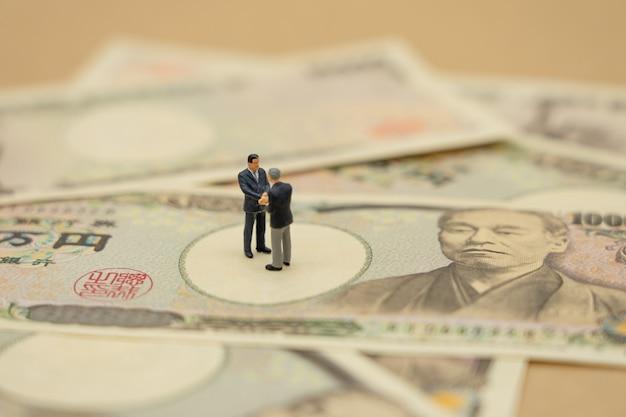 ミニチュア2人ビジネスマン握手10,000円相当の日本の紙幣の上に立つ Premium写真