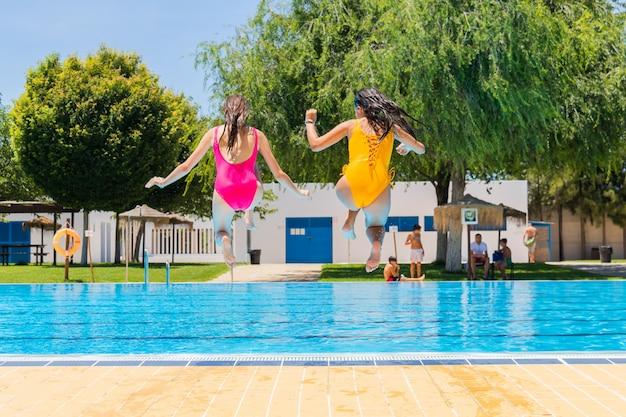 スイミングプールでジャンプ2人の10代の少女。スイミングプールに飛び込む2人の女の子 Premium写真