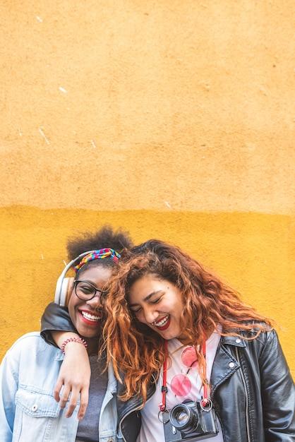 黄色の壁の上に一緒に立っている2人の10代ラテン系の女の子 Premium写真