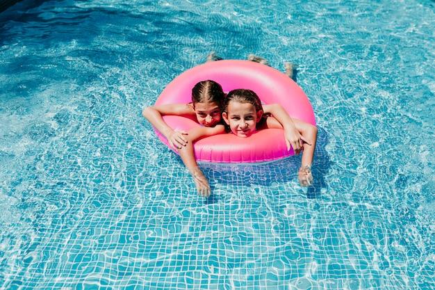 プールでピンクのドーナツに浮かぶ2つの美しい10代の女の子。笑顔。楽しさと夏のライフスタイル Premium写真