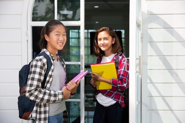 2人の10代のアジアとヨーロッパの学生友人女の子は大学または学校に行くことを幸せにします Premium写真