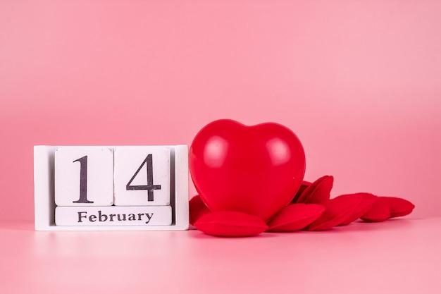 ピンクの2月14日カレンダーと赤いハート形の装飾。愛、結婚式、ロマンチックで幸せなバレンタインの日の休日の概念 Premium写真