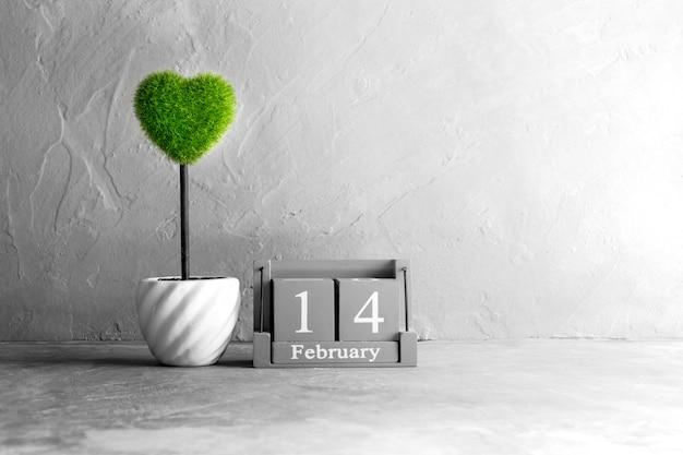 木製のテーブルの上の緑の心と2月14日のヴィンテージの木製カレンダー Premium写真