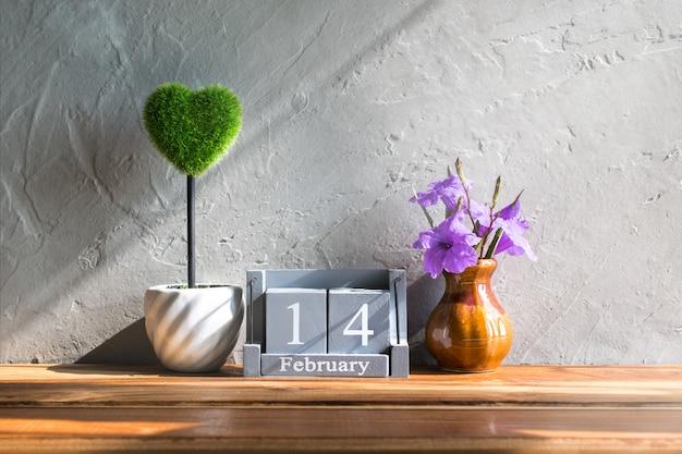 木製テーブル愛とバレンタインデーの概念の背景、背景に緑の心を持つ2月14日のビンテージ木製カレンダー。 Premium写真