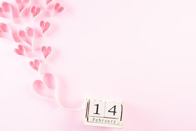 ピンクのパステル紙の背景に木製カレンダー2月14日とピンクの紙の心 Premium写真