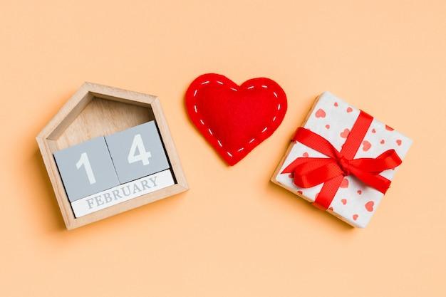 木製カレンダー、休日の白いギフトボックス、カラフルな赤い繊維心の組成。 2月14日。バレンタイン・デー Premium写真