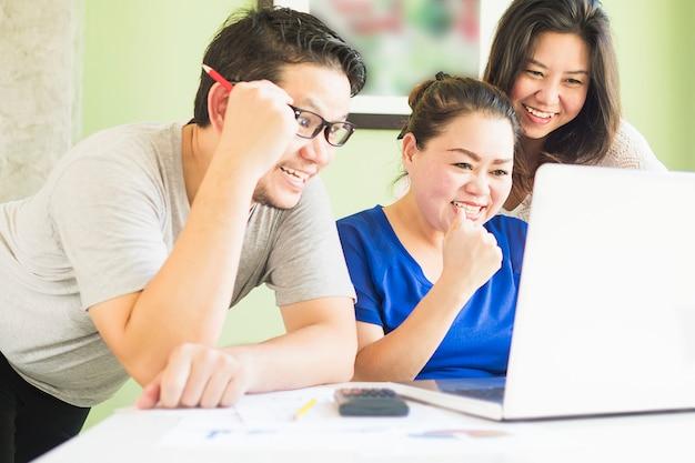 2人の女性と1人の男性が近代的なオフィスのコンピューターを楽しく見ています。 無料写真
