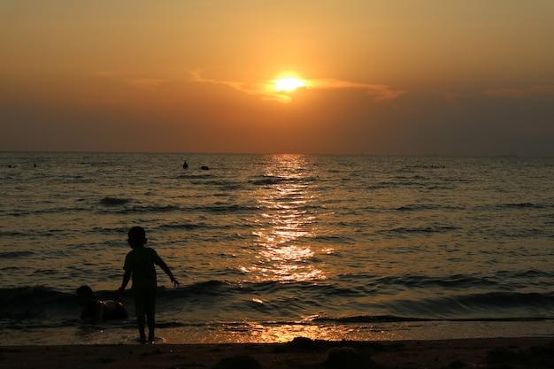 シルエット2人の子供が海の夕日、1人の子供がビーチの上に立つ Premium写真