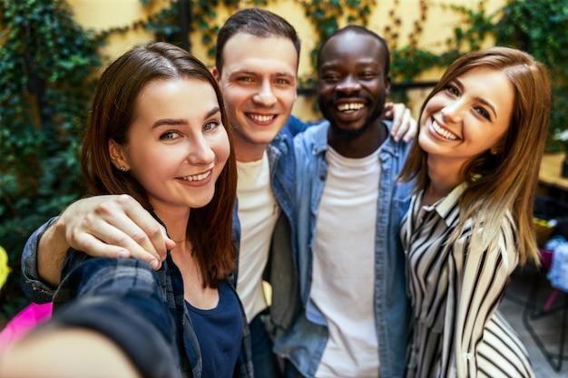 2人の女の子と2人の男の子が屋外で自分撮り写真を撮っており、お互いをハグし、誠実な笑顔で 無料写真