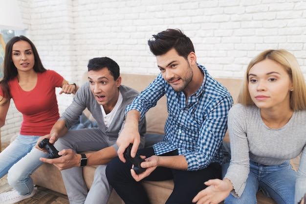 ゲームコンソールで2人の男と2人の女の子がプレイします。 Premium写真