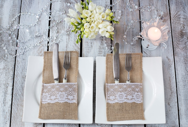 白い木製のテーブル、2つのプレート、キャンドル、フォークとナイフ、花瓶 - お祝い背景に花(誕生日、結婚式、3月8日、ロマンチックなディナー) Premium写真