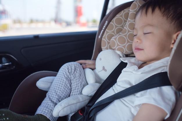 現代の自動車の座席で眠っているかわいいアジア人2  -  3年幼児の赤ちゃん男の子子供 Premium写真