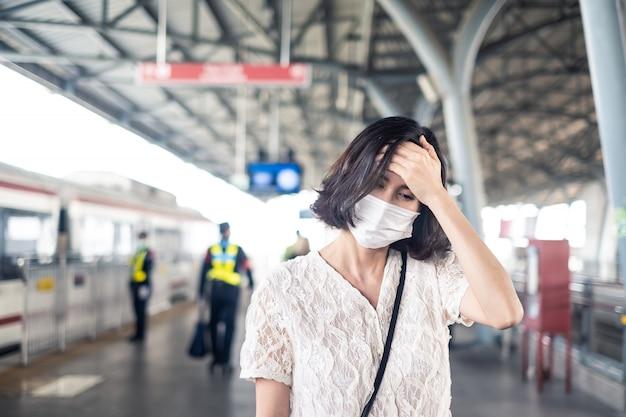 Азиатская женщина, носящая маску для предотвращения сумеречных часов. 2.5. сильное загрязнение воздуха и распространение коронавируса или ковид-19 по всей азии с головной болью на небесном поезде. Premium Фотографии