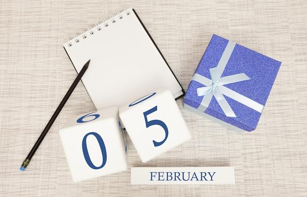 2月5日のトレンディな青色のテキストと数字、および箱入りのギフトのカレンダー。 Premium写真