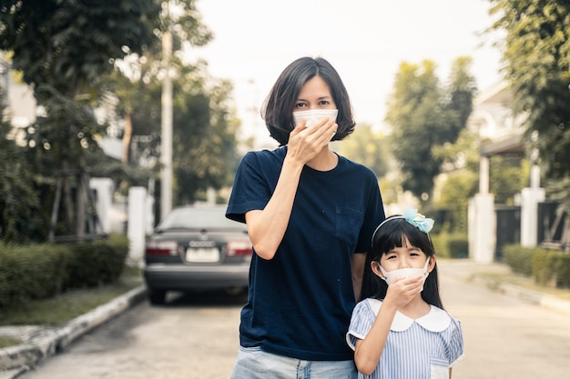 Маска азиатской женщины и маленькой молодой дочери нося для предотвращает загрязнение воздуха сумрака 2.5 плохое. Premium Фотографии