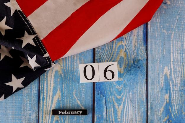 古い木の板に星とストライプのアメリカ国旗を美しく振る2月6日カレンダー。 Premium写真