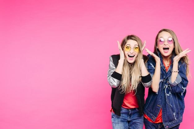 2人のbestgirlriendsは、頬に手を広げて口を開けて、叫んで興奮しました。 Premium写真