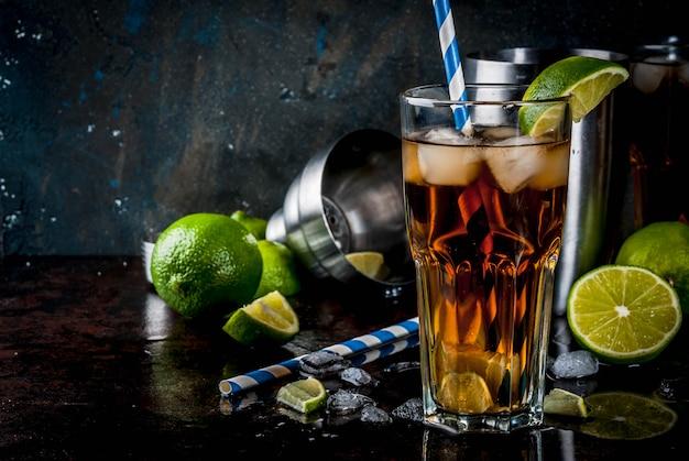 キューバリブレ、ロングアイランドまたはアイスティーカクテル、強いアルコール、コーラ、ライム、アイス、2杯のガラス、暗いcopyspace Premium写真