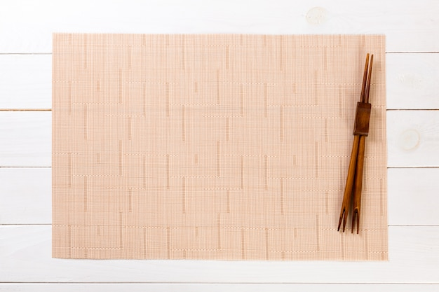 2 палочки суш с пустой коричневой бамбуковой циновкой или деревянной плитой на белом деревянном взгляд сверху с copyspace. пустая азиатская еда фон Premium Фотографии