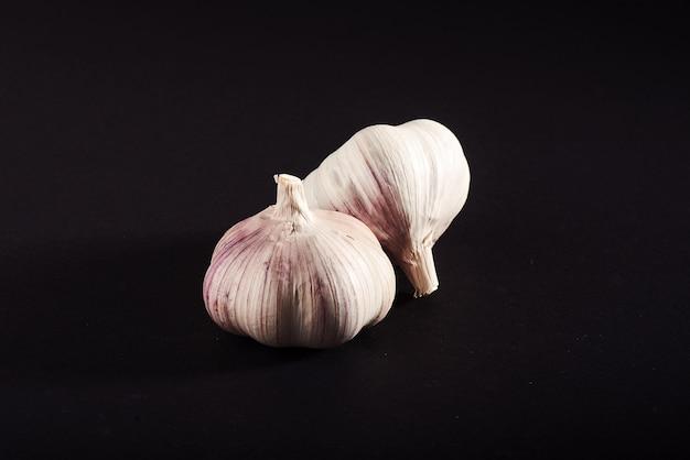 2 bulbi di aglio fresco su fondo nero Foto Gratuite