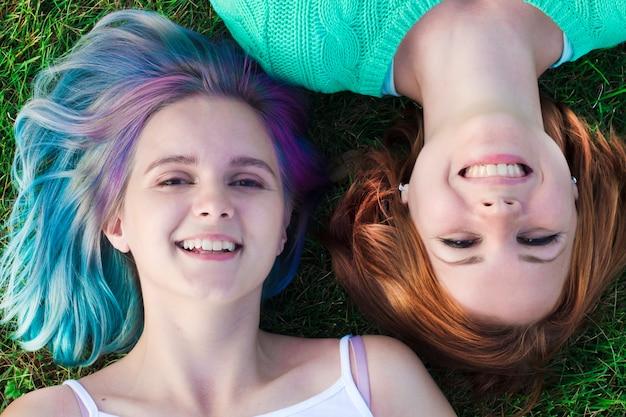 公園の芝生の上に横たわる2つの幸せな陽気な若いレズビアンの女の子。上面図。カラフルな髪、笑顔の友人とかなりティーンエイジャー。 lgbtの概念、素敵なレズビアンカップル屋外。美しい女性。 Premium写真