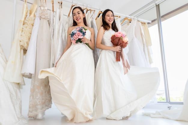2人の花嫁は白いドレス。結婚式の瞬間に幸せなアジアの同性愛カップルの肖像画。概念lgbtレズビアン。 Premium写真