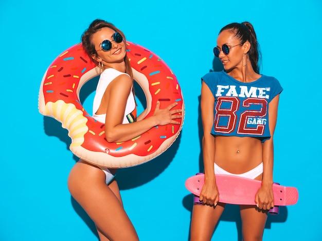 夏のパンツとトピックの2人の美しい笑顔のセクシーな女性。サングラスの女の子。カラフルなペニースケートボードを楽しんでいるポジティブなモデル。ドーナツliloインフレータブルマットレス付き 無料写真