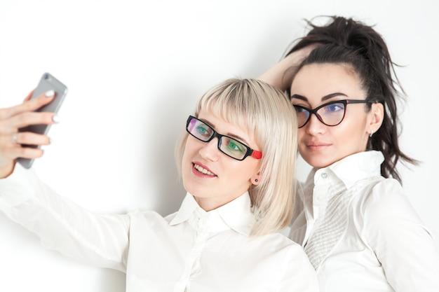 白いシャツとメガネの2人の女の子が電話でselfieを行う Premium写真