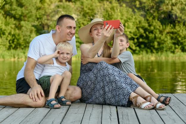 父の母と2人の幼い息子が座ってselfieを取っている Premium写真