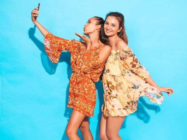夏のヒッピードレスで2人の若い笑顔ヒップスター女性。スマートフォンでselfieセルフポートレート写真を撮る女の子。スタジオの青い壁の近くでポーズをとるモデル。女性は空気キスを与えます。 無料写真