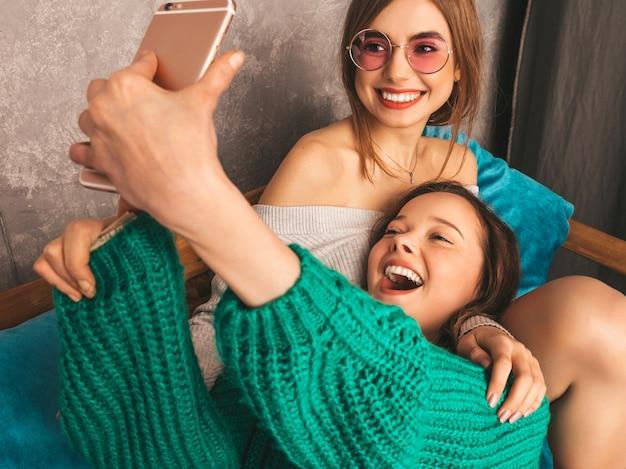 トレンディな夏服で2人の若い美しい笑顔の豪華な女の子。セクシーな屈託のない女性がインテリアでポーズとselfieを撮影します。スマートフォンを楽しんでいるポジティブなモデル。 無料写真