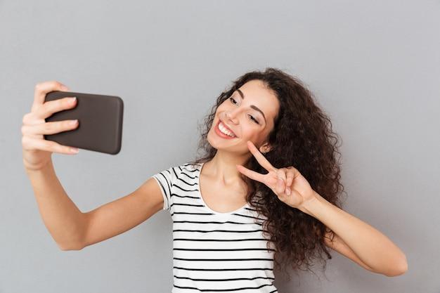 笑みを浮かべて、2本の指で勝利ジェスチャーを行う彼女のスマートフォンでselfieを作る白人の外観を持つ素晴らしい女性 無料写真