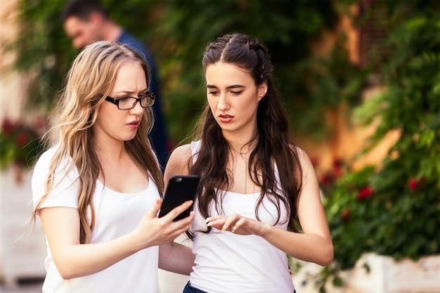 2人の若い白人の女の子は、smthについて議論し、深刻な顔でスマートフォンを探しています 無料写真