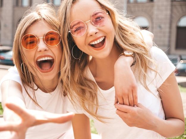 トレンディな夏の2人の若い美しいブロンド笑顔流行に敏感な女の子白いtシャツ服。 無料写真