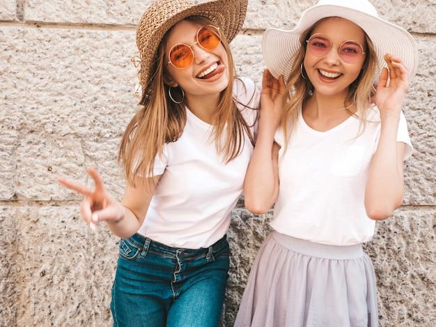 トレンディな夏の2人の若い美しいブロンド笑顔流行に敏感な女の子白いtシャツ服。壁の近くの通りでポーズをとる女性。 。ピースサインを表示 無料写真