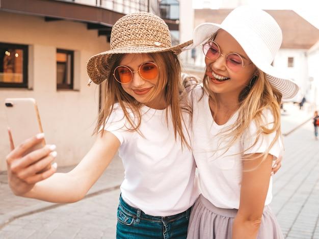 夏に2人の若い笑顔ヒップスターブロンド女性白いtシャツ服。スマートフォンでセルフポートレート写真を撮る女の子。 無料写真