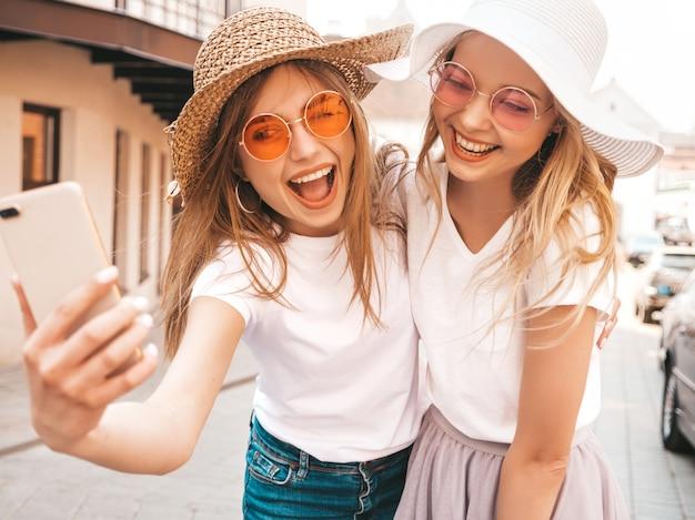 夏に2人の若い笑顔ヒップスターブロンド女性白いtシャツ。スマートフォンでセルフポートレート写真を撮る女の子。通りの背景でポーズをとるモデル。女性は肯定的な感情を示しています。 無料写真