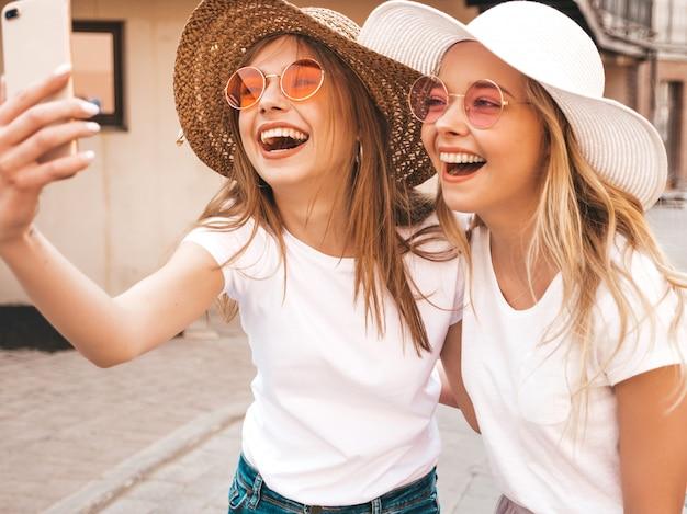 夏に2人の若い笑顔ヒップスターブロンド女性白いtシャツ。スマートフォンでセルフポートレート写真を撮る女の子。通りの背景にポーズをとるモデル。 無料写真