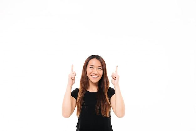カメラを見て、2本の指で上向きに指している黒いtシャツで陽気なアジアの少女 無料写真