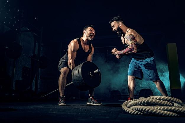 ジムでトレーニング2つの筋肉のひげを生やしたtattoed選手 Premium写真