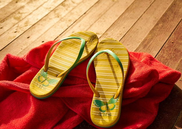 2 yellow sandals and a red towel Free Photo