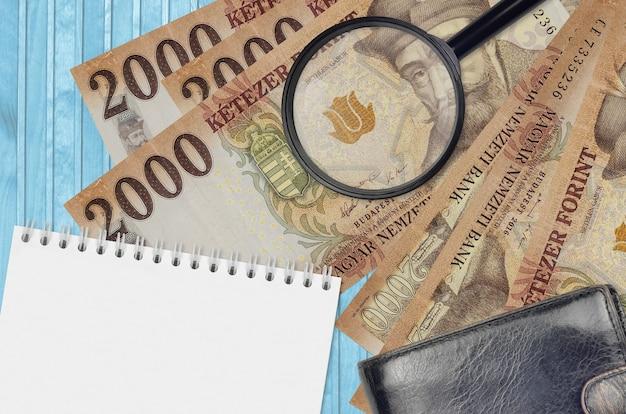 Банкноты 2000 венгерских форинтов и увеличительное стекло с черным кошельком и блокнотом Premium Фотографии