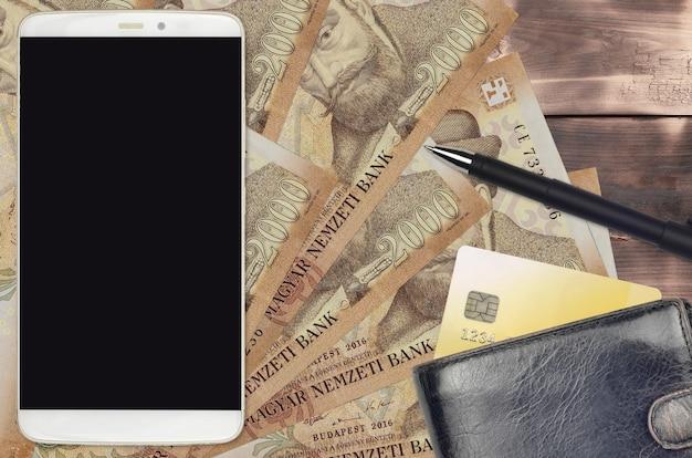 Банкноты 2000 венгерских форинтов и смартфон с кошельком и кредитной картой Premium Фотографии